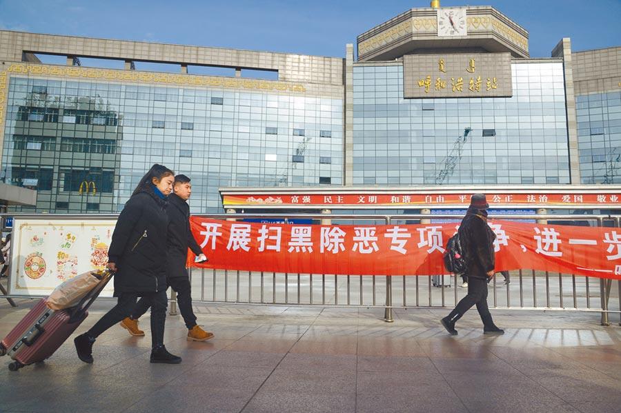1月7日,民眾從呼和浩特火車站前的掃黑除惡宣傳橫幅前走過。(中新社)