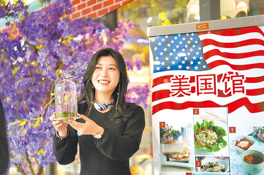 2月22日,重慶保稅港區一帶一路沿線國家特色商品貿易及文化周,美國館工作人員展示特色產品。(中新社)