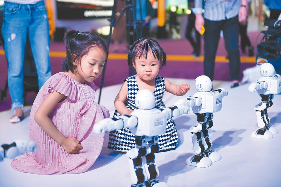 2019年5月18日,投貿博覽會在江西省南昌市開幕,小朋友參觀展出的機器人。(新華社)