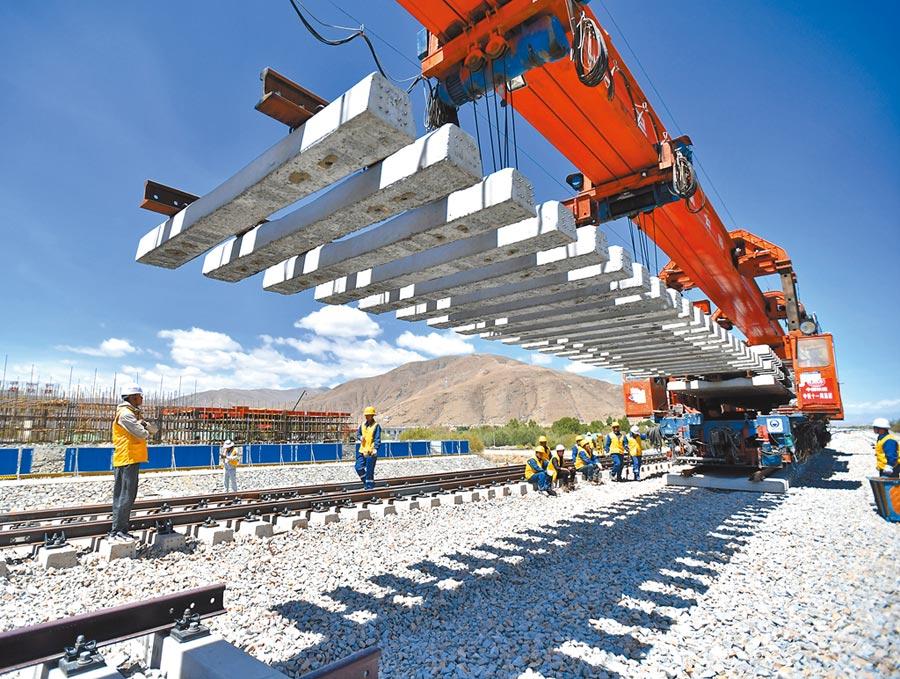6月6日,負責拉林鐵路鋪軌的中鐵十一局集團工人在現場作業。(新華社)