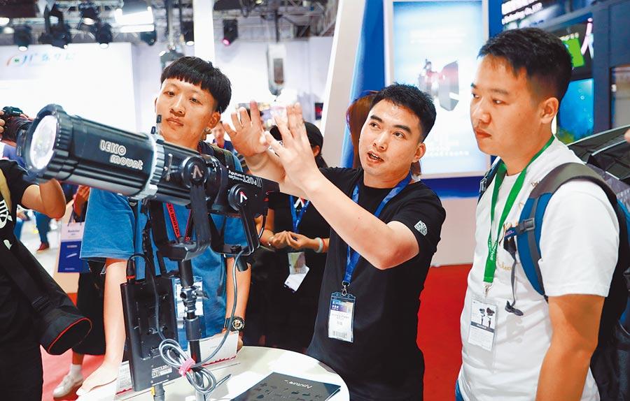 北京國際廣播電影電視展上,商代表向民眾講解新式設備。(新華社資料照片)
