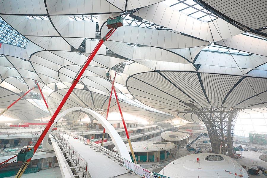 2018年12月29日,北京大興國際機場主航站樓內,施工人員進行屋頂裝飾裝修工作。(新華社)