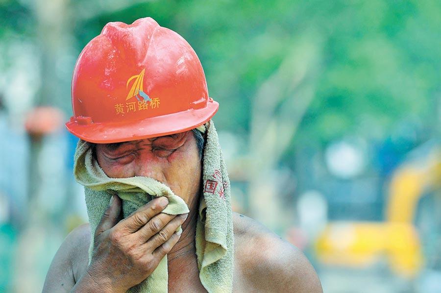 一名工人在建設工地上擦汗。(新華社資料照片)