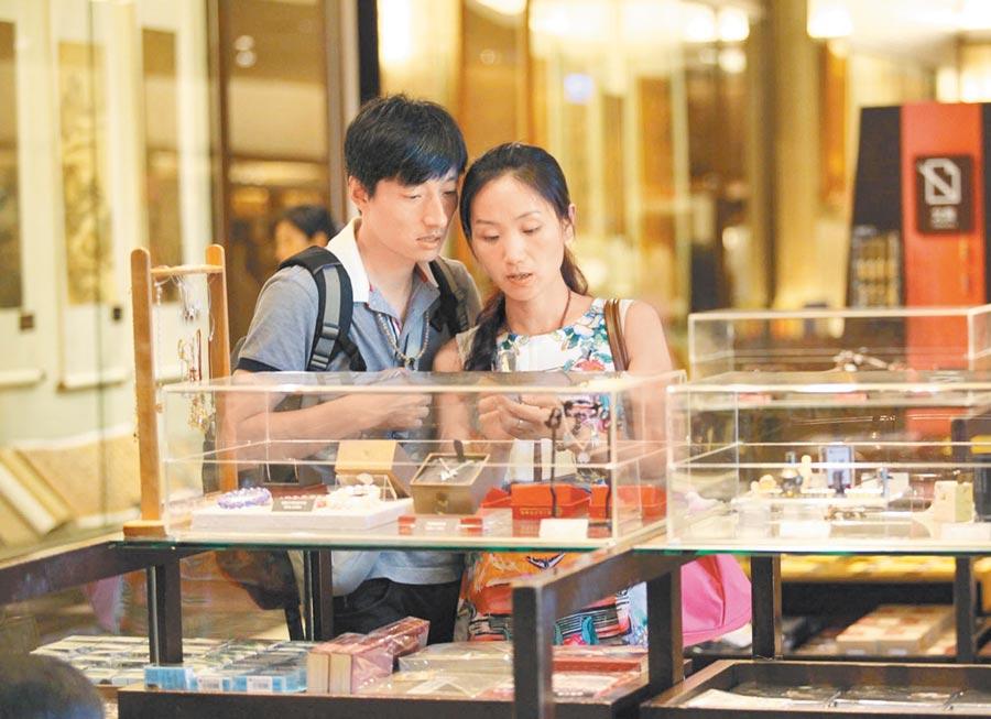 故宮文物結合文創吸引關注。圖為兩位觀光客在台北故宮禮品店選購紀念品。(本報系資料照片)