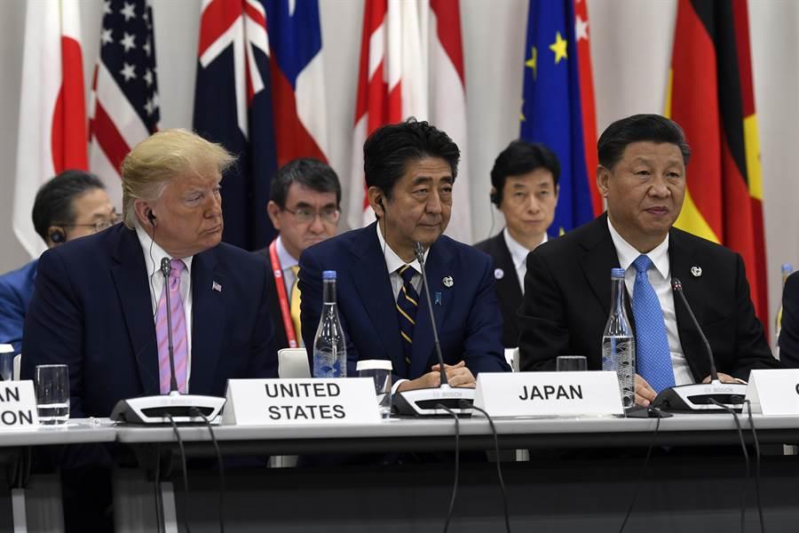 G20大阪峰會一場特別會議上,讓日本首相安倍晉三、美國總統川普及中國大陸國家主席習近平並肩而坐,三人表情十分僵硬,讓網友笑稱安倍「左右為難」。(美聯社)