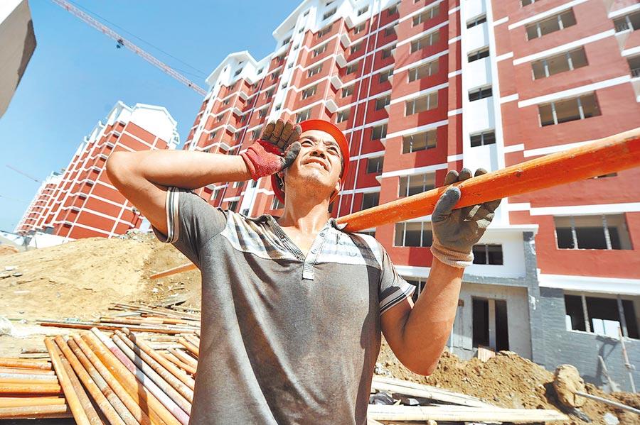 商業地產庫存難消化,閒置問題嚴重。圖為銀川一位工人在建設工地上搬運鋼筋。(新華社資料照片)