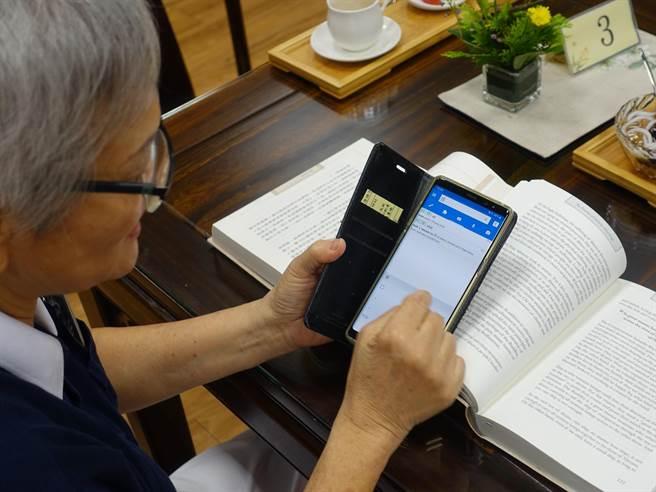 廖金鳳把看不懂的中文字依樣畫葫蘆「寫」在翻譯APP,再點選跟書籍「外觀」一樣的文字,了解英文的意思。(圖/慈濟基金會提供)