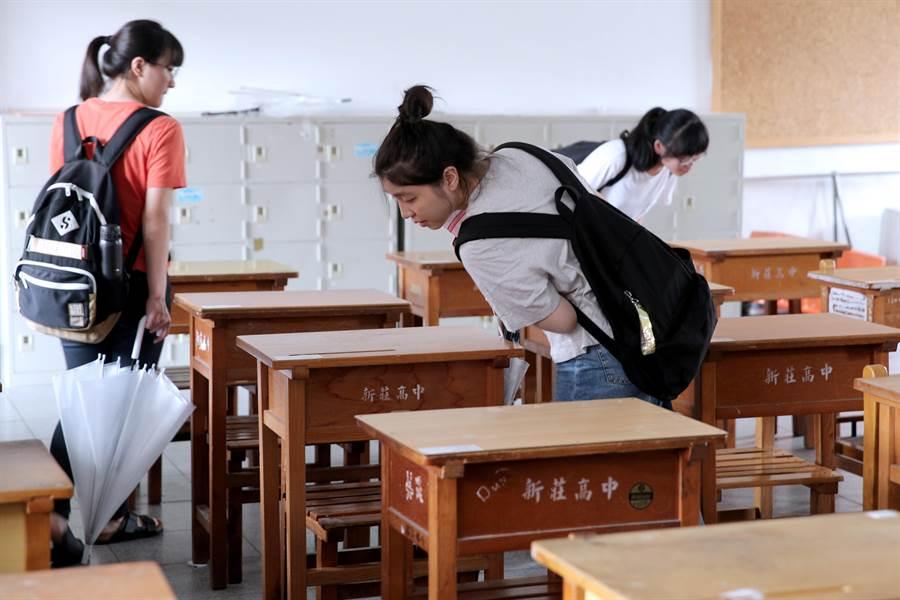 考生們仔細看著桌上的名條,找尋自己的座位。(黃世麒攝)
