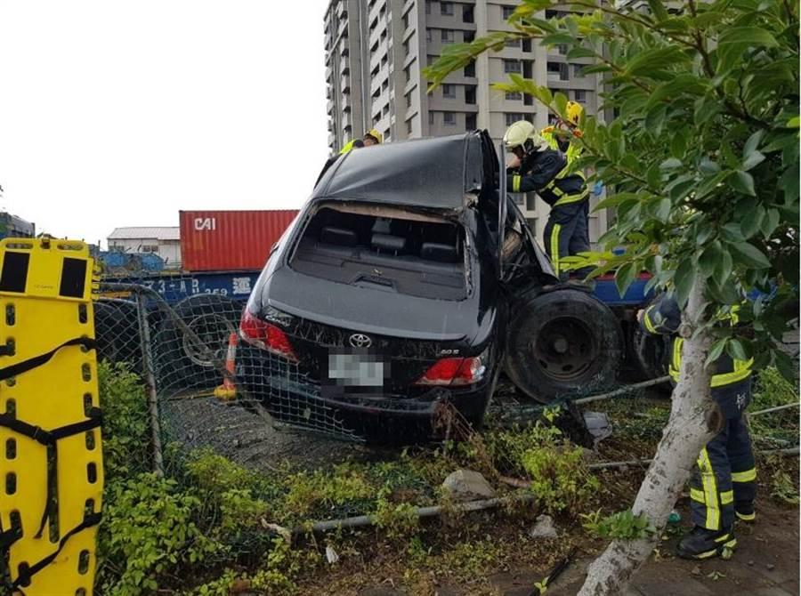 男子駕駛小客車擦撞路邊拖板車,整台車疊上後拖板。(陳淑娥翻攝)