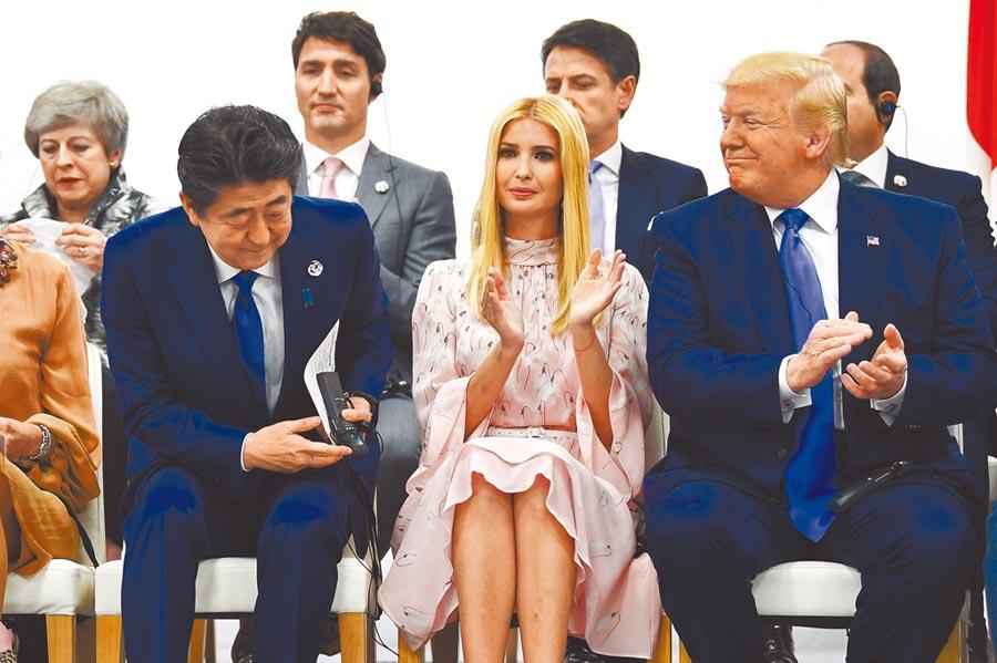 陪同美國總統川普(右)出席20國集團(G20)峰會的第一千金、白宮資深顧問伊凡卡(中)29日出席一場活動,亮麗的外型再度成為全場焦點。坐在她旁邊的日本首相安倍晉三(左)等在場男性都緊盯著她看。(法新社)