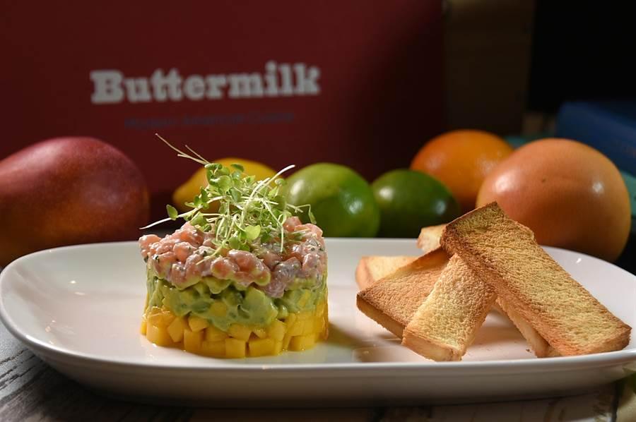 〈Buttermilk〉新主廚Jason周建宏設計的夏季新菜〈鱒鮭魚酪梨芒果塔塔〉,用了芒果丁、酪梨丁與挪威鱒鮭魚丁堆疊共構,並用萊姆酸奶醬和酪梨醬穿針引線,形色味皆很誘人。(圖/姚舜)