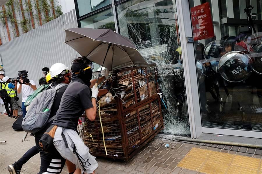 香港七一遊行,示威者試圖以鐵車衝撞立法會玻璃大門,鎮暴警察在大樓內戒備。(圖/路透社)