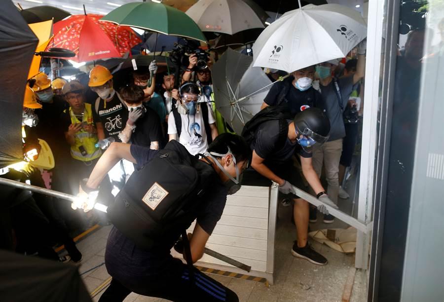 香港抗議修訂《逃犯條例》風波未平息,下午大批示威者在立法會外抗議,並用堅硬物品衝破立法會玻璃門,不久之後後再撬開大堂鐵閘衝進立法會大樓內。(圖/路透)