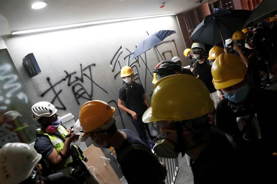 香港示威者攻入立法會大會議事廳,在牆上噴上字句、塗污特區區徽。(圖/路透)