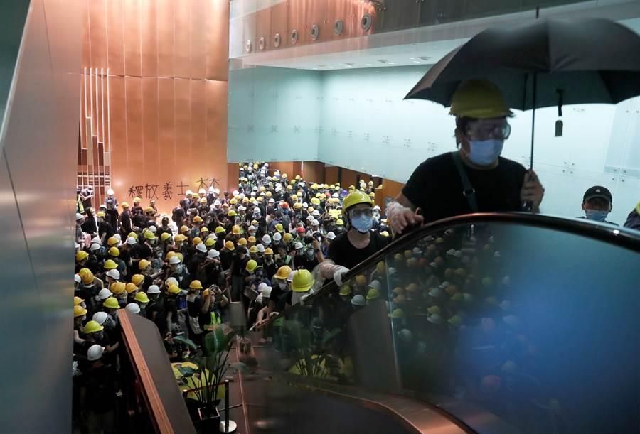 大量香港抗議人士翹開鐵柵後衝入立法會大堂內,在牆上噴漆。(圖/路透)