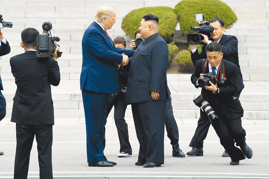 美國總統川普(中左)和北韓最高領導人金正恩(中右)6月30日在板門店會面後,兩人走到北韓一側,並在多名攝影記者拍攝下,再次握手。(美聯社)