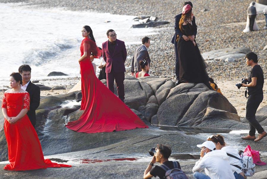 在福建廈門一處海灘礁石上,美麗的海邊風光吸引了多對新人前來拍攝婚紗照。圖/中新社