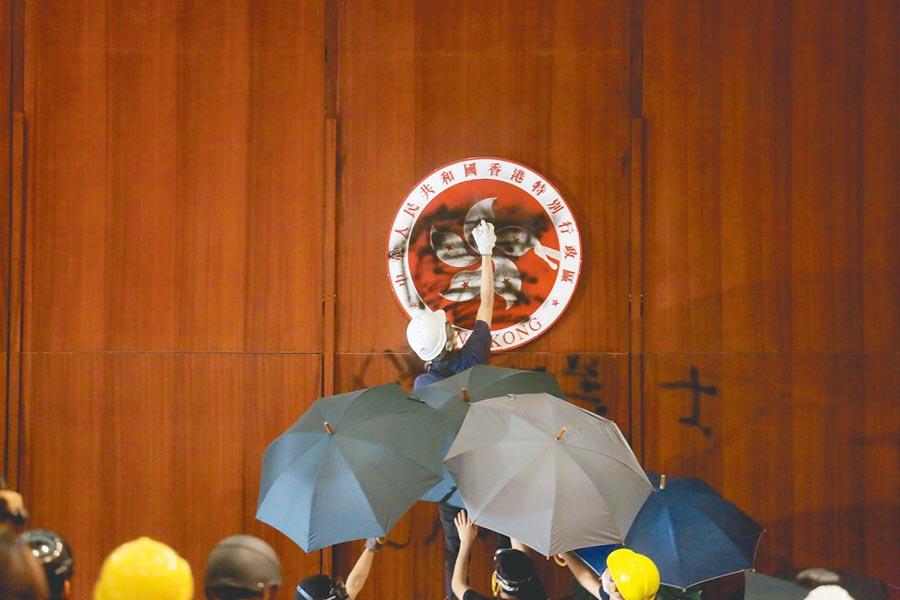 一名香港示威者在香港特別行政區區徽上塗鴉。(法新社)