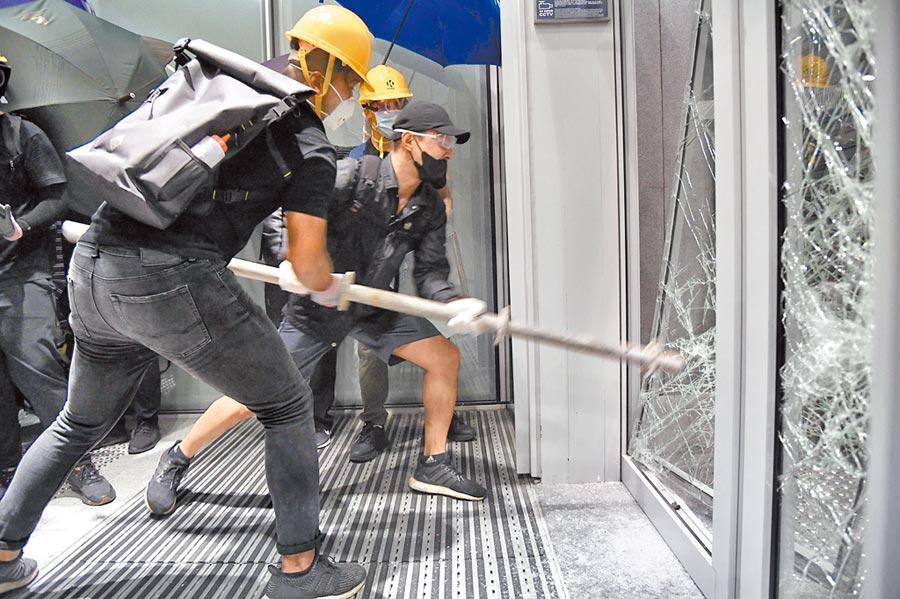 港民以鐵籠車和鐵枝等武器破壞立法會玻璃大門。(中新社)