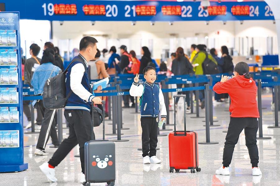 準備出境旅遊的廣州市民在拍照留念。(新華社資料照片)