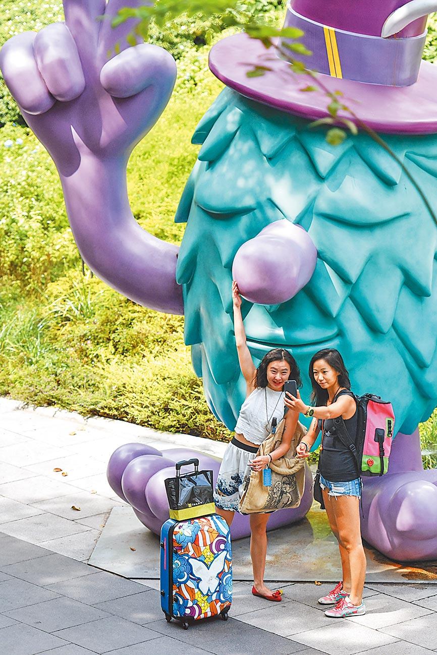 中國遊客在曼谷與一件卡通藝術作品合影。(新華社資料照片)