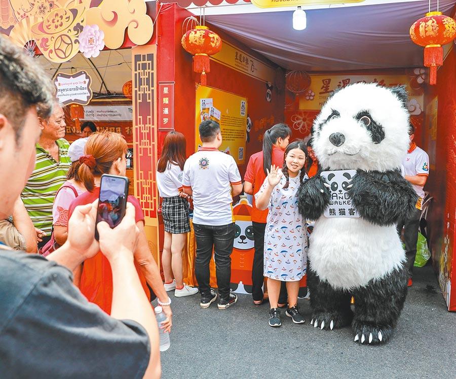 中國遊客在泰國曼谷唐人街與貓熊人偶合影。(新華社資料照片)