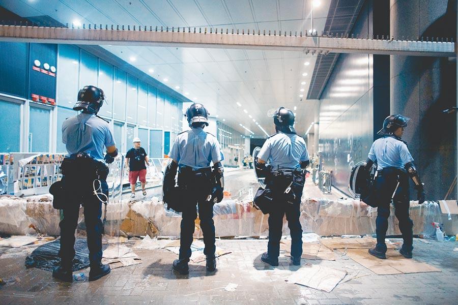 香港1日舉行的反送中遊行失控,一批示威者衝進立法會大肆破壞,警方在半夜展開驅離,直到凌晨才完成現場清理。鎮暴警察2日在立法會大樓外排成一列,地上仍可見示威過程遺留的垃圾。(路透)
