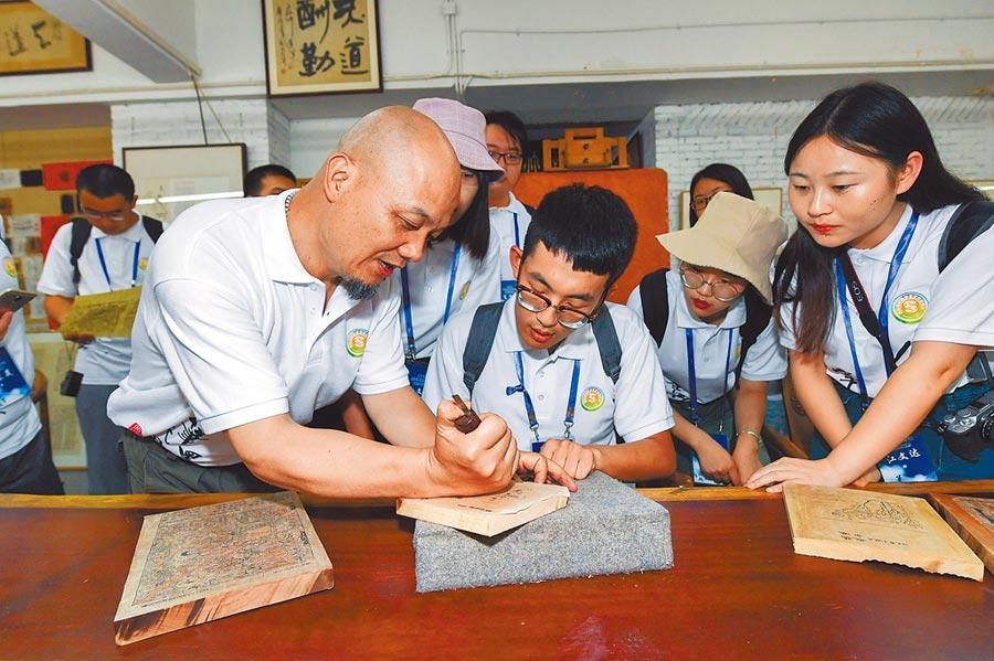 2018年7月29日,兩岸大學生文化體驗營在杭州啟動,首站到杭州十竹齋藝術館感受國家級非物質文化遺產──木版水印技藝的獨特魅力。(新華社)