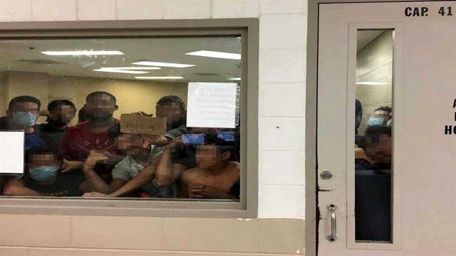 美國國土安全部2日公布驚人報告與畫面,顯示邊界移民拘留中心超收移民,導致人滿為患、衛生條件糟糕。上圖顯示這間房間原本僅能容納41人,最後卻滯留了88名成年男性,明顯超收1倍。有移民在紙板寫下自己已遭拘留的時間。(圖/路透社、國土安全部)
