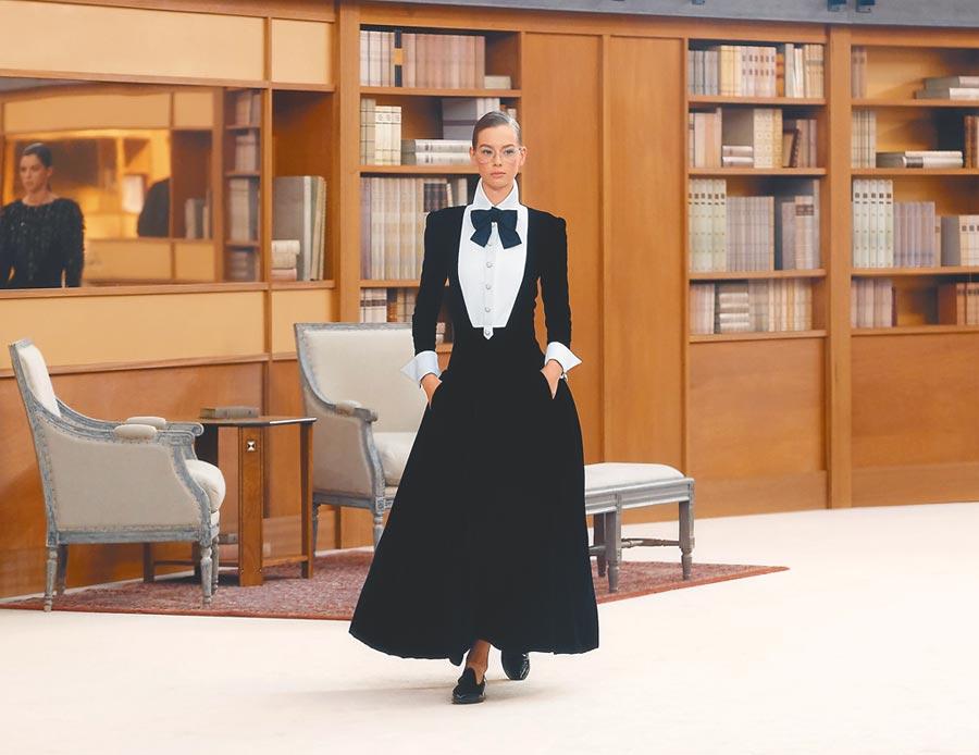 模特兒穿中性風的黑白色套裝,戴金框眼鏡,充滿復古風情。(CHANEL提供)