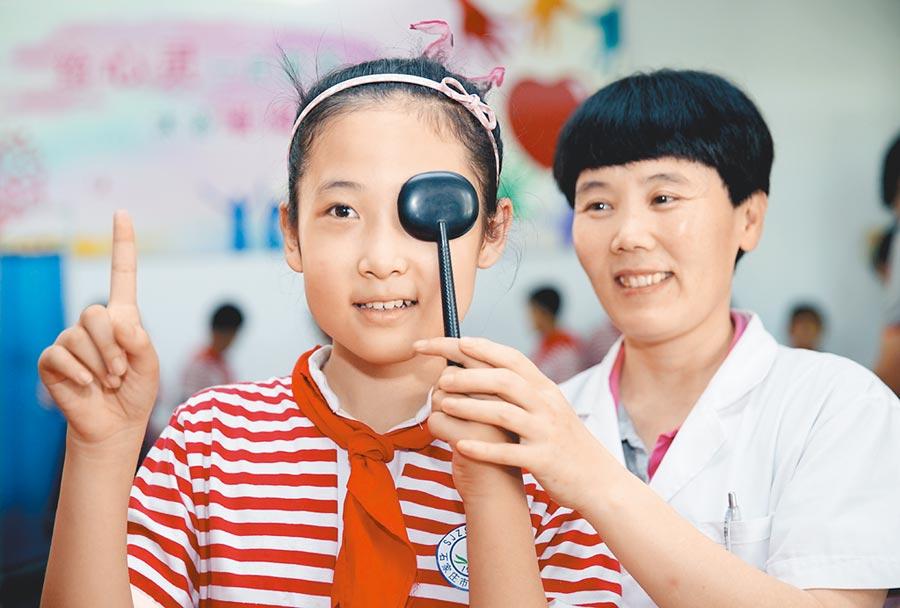在石家莊市西里小學,醫護人員為小學生進行視力檢查。(新華社)