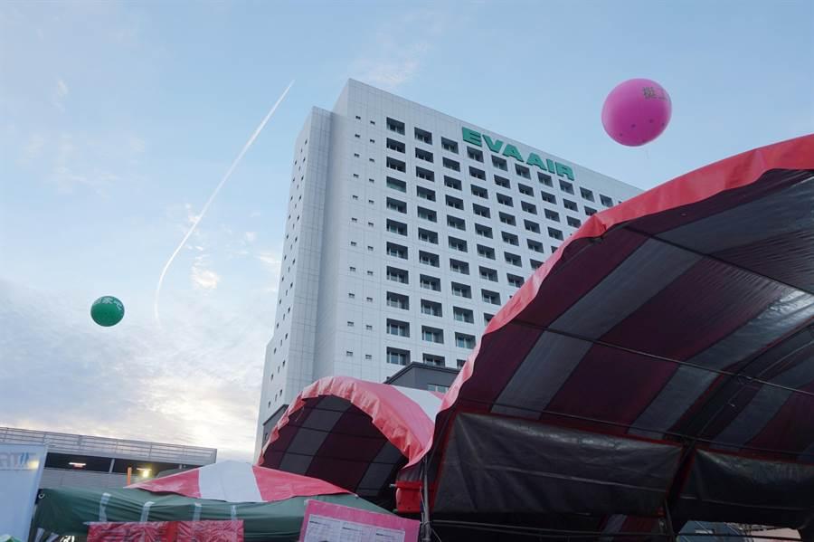 空服員苦行出發時,綠色與粉紅色的大氣球在長榮大樓外面對立飄揚。(甘嘉雯攝)