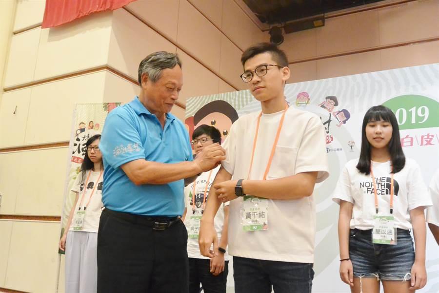 水土保持局副局長林長立替各駐村團隊代表別上徽章,宣布正式啟動駐村計畫。(巫靜婷攝)