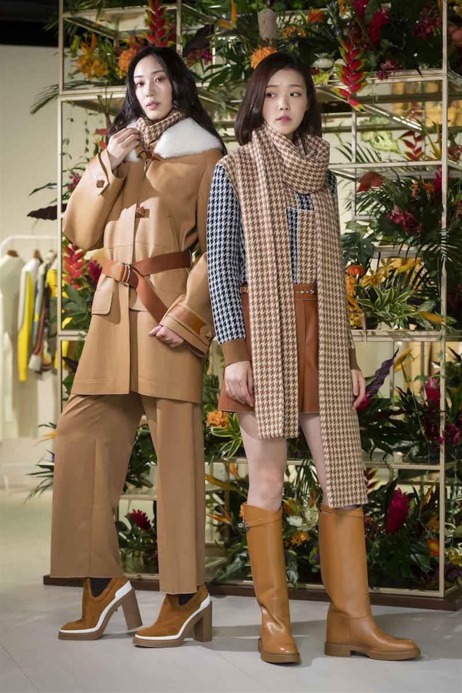 愛馬仕秋冬女裝融合新古典、新騎士風主義。左側模特兒的棕赭色可拆卸式剪羊毛皮衣領鹿皮大衣,靈感來自男士飛行員夾克,38萬8200元。棕色可拆卸式衣領喀什米爾羊絨套衫6萬6900元、棕赭色初剪羊毛高腰八分褲5萬6100元。 右側模特兒的棕色蘇格蘭羊絨提花針織毛衣,參考馬術騎士服的幾何色塊,5萬1800元。棕色蘇格蘭羊絨提花針織圍巾5萬4000元,焦糖棕色小牛皮短褲17萬2600元。(HERMES提供)