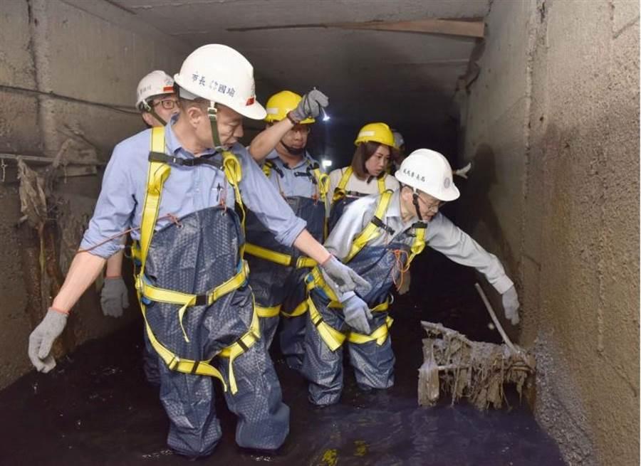 高雄市長韓國瑜(前)5日親自出穿上青蛙裝進入下水道視察,看到淤塞近40公分,轉角處都是碎石頭,還有一些無法想像的淤塞物。 (高市府提供)