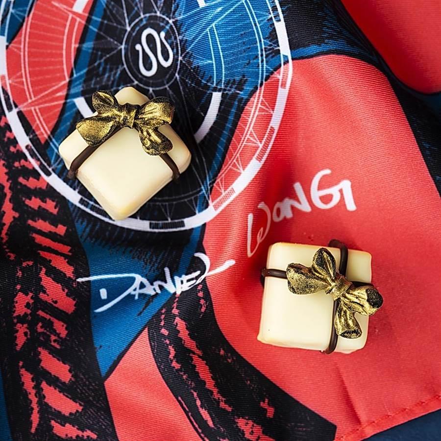 台北遠東飯店馬可波羅酒廊推出《啟程Journey to 100 Prints》聯名下午茶,圖為禮物造型百香果白巧克力。(圖/台北遠東國際大飯店)