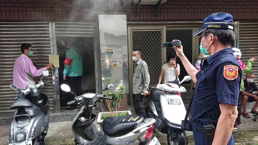 台南市衛生局6日在開山里進行大規模地毯式噴藥,配合警方蒐證破門強制防疫。(程炳璋攝)