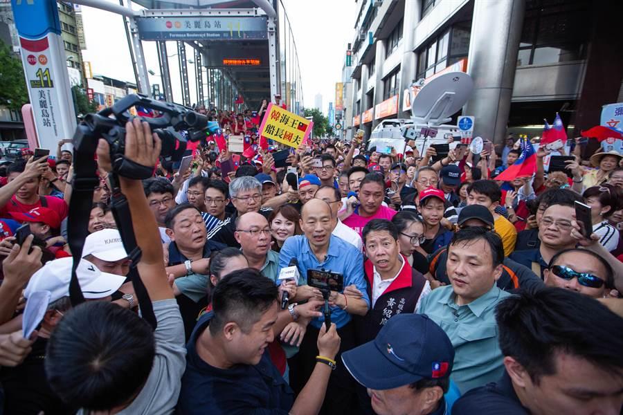 高雄市長韓國瑜改從較遠的捷運站步行至六合夜市,一現身立刻引爆韓粉歡呼,現場數百人一湧而上,讓滿身大汗的韓國瑜無法前進、也驚訝不已。(袁庭堯攝)