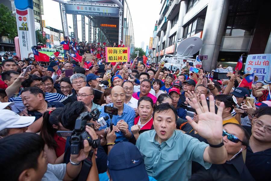 高雄市長韓國瑜改從較遠的捷運站步行至六合夜市,一現身立刻引爆韓粉歡呼,現場數百人一湧而上,讓滿身大汗的韓國瑜無法前進,透過警方人龍強勢開道依然寸步難行。(袁庭堯攝)