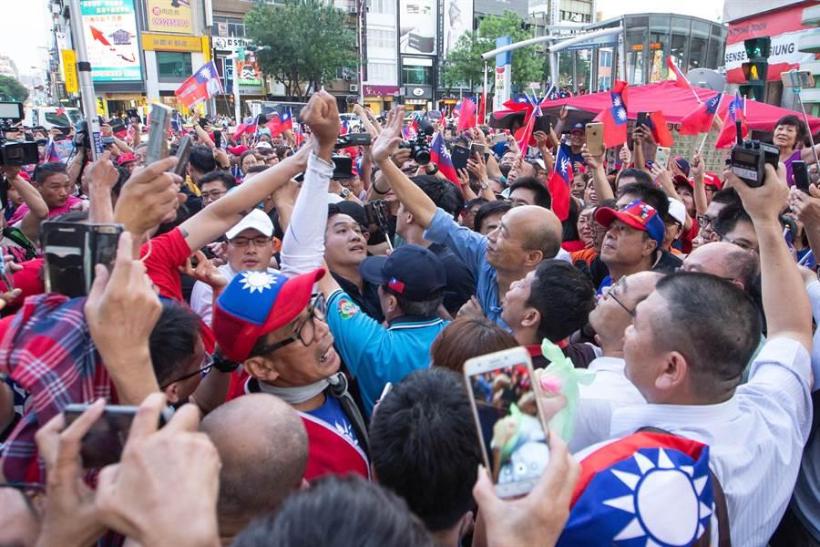 高雄市長韓國瑜好不容易透過警方人力強勢開道、稍微擠進六合夜市入口,礙於現場韓粉過度熱情,只好與身邊韓粉致意後,驅車離去。(袁庭堯攝)