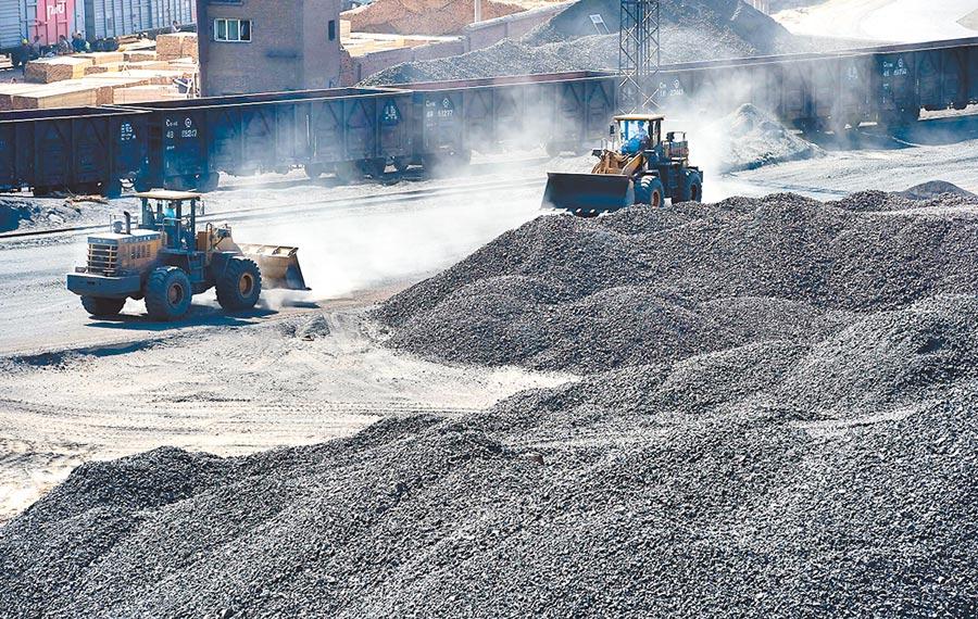 終結瘋漲,大陸鐵礦石期貨大跌,圖為工程車輛在二連浩特鐵路貨場裝運進口鐵礦石。(新華社資料照片)