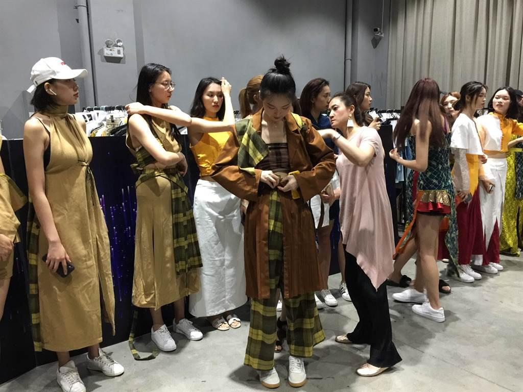 玄奘大學時尚設計學系施文瑛主任親自調整與每位模特兒的服裝。(楊宜臻攝)