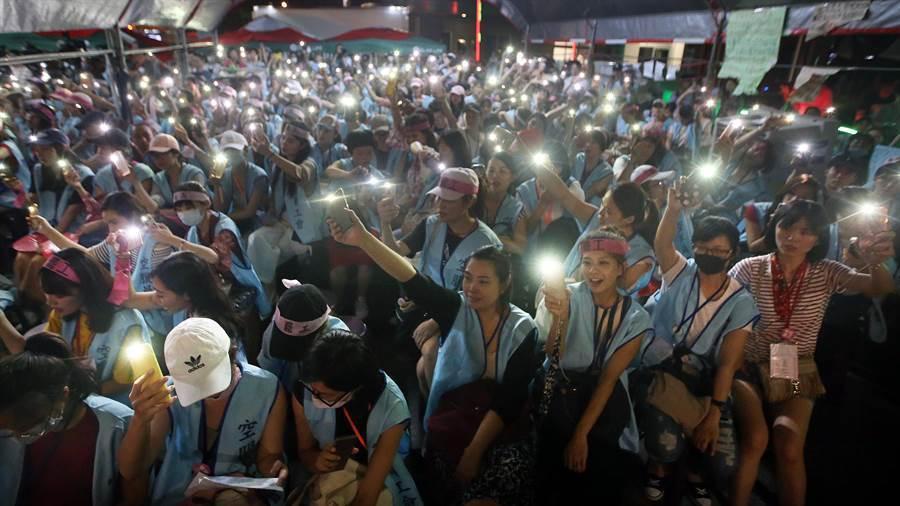在長榮航空南崁總部前靜坐的空服員,打開手機燈光,高唱「美麗島」慶祝罷工成功。(范揚光攝)