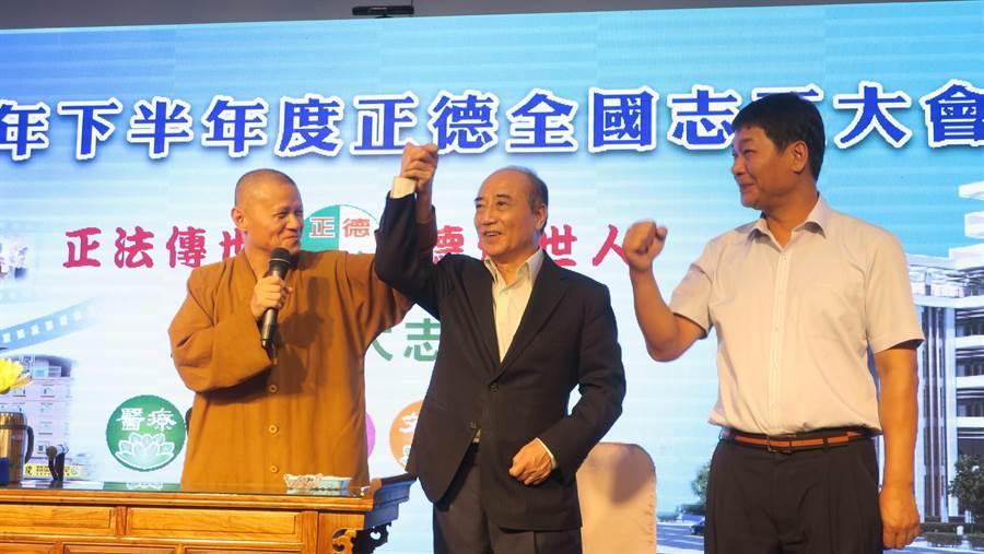 正德慈善基金會常律法師(左起)舉起王金平的手,要全體志工和全國的幹部會長踴躍支持王選總統,右為高雄市議員朱信強。(謝瓊雲攝)