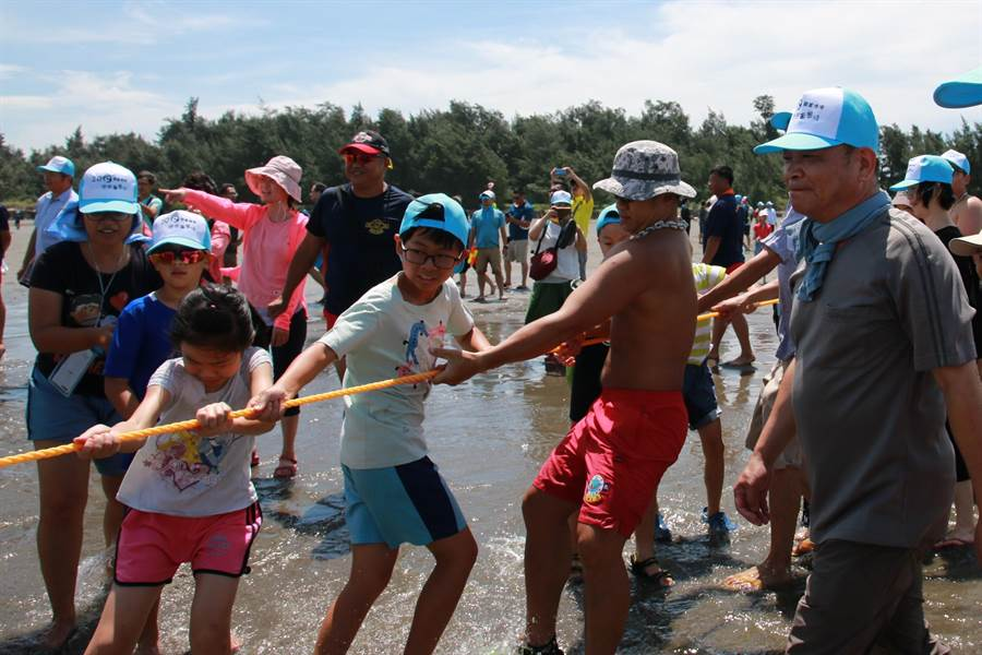 大人小孩合力拉漁網上岸,頂著豔陽玩得不亦樂乎。(何冠嫻攝)