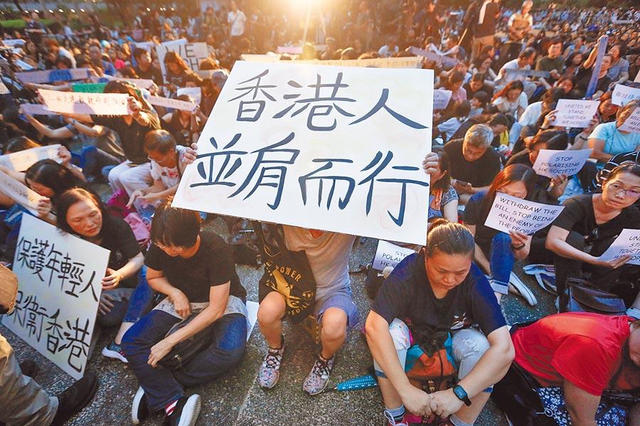 反對修訂逃犯條例的數千名「香港媽媽」5日晚在中環集會,促請政府放下傲慢,回應年輕人訴求。圖為一名婦人拿著寫有「香港人並肩而行」的牌子,參加這場活動。(美聯社)