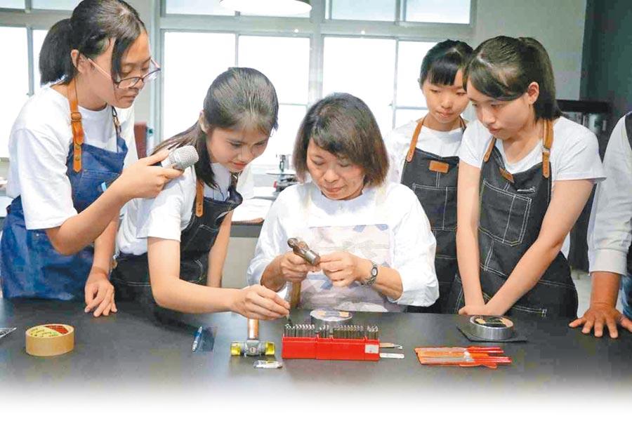 市長體驗金工課程,與學生利用鐵槌敲擊打字,製作一個專屬的鑰匙圈。圖片提供嘉義市政府