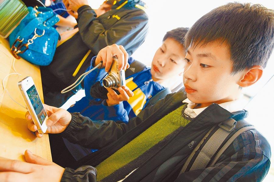 大陸小學生在玩手機。(新華社資料照片)