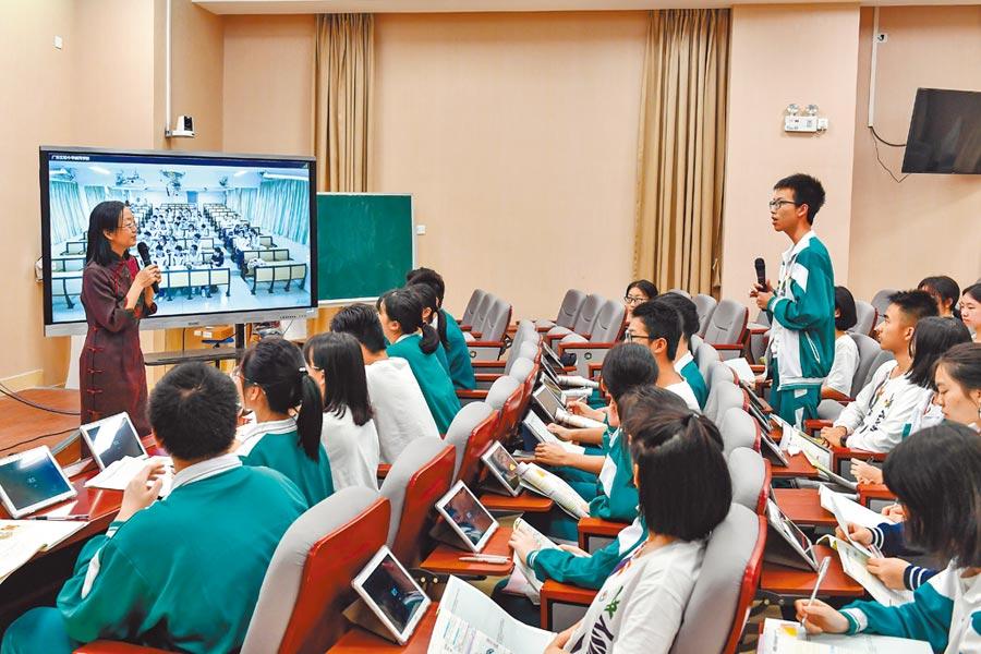3月29日,廣東某中學老師使用「5G+遠程」互動教學系統為本班和分校的同學上課。(中新社)