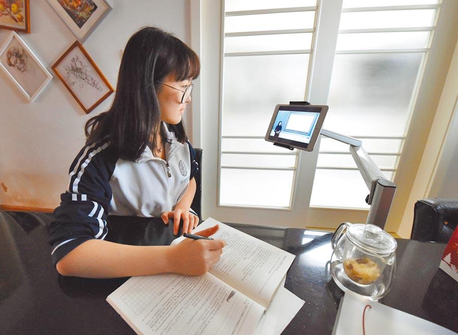 大陸某高一學生在家觀看學校的直播課程。(新華社)